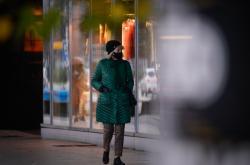 Žena v roušce jde po ulici v polské Varšavě
