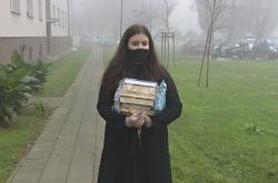 Knihovnice nese zabalené knihy čtenáři