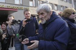 Jurij Dmitrijev mluví s lidmi před budovou soudu