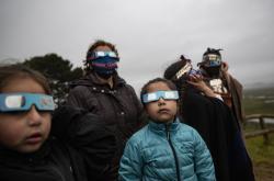 Lidé sledují úplné zatmění slunce 14. prosince 2020 v Piedra del Aguila v Argentině