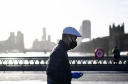 Muž s rouškou na Westminsterském mostě v Londýně