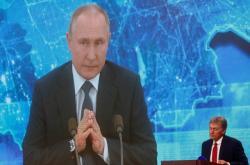 Šéf Kremlu Putin na obrazovce přenosu z tiskové konference, v rohu mluvčí Peskov