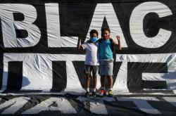 Dva chlapci stojící na transparentu hnutí Black Lives Matter, které v roce 2020 protestovalo za práva Afroameričanů v USA