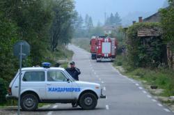 Policie a hasiči na příjezdové k cestě ke skladu v bulharské obci Gorni Lom po výbuchu v říjnu 2014