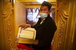 Ujgurský duchovní drží v ruce korán
