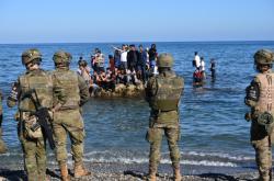 Španělští policisté a migranti na pobřeží v Ceutě