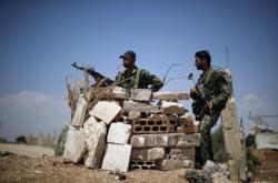 Syrští vojáci hlídkují nedaleko Damašku