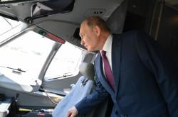 Vladimir Putin si prohlíží vybavení stíhačky