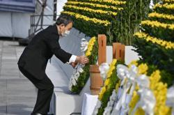 Japonský premiér Jošihide Suga klade věnec na pomník