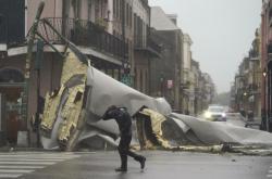 Muž prochází ve Francouzské čtvrti města New Orleans kolem stržené střechy