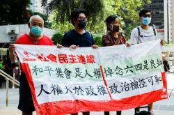 Prodemokratičtí aktivisté křičí slova podpory před budovou soudu