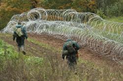 Lotyšští vojáci stavějí dočasnou hraniční bariéru