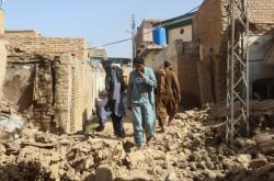 Obyvatelé města Harnai procházejí troskami zřícených budov
