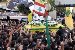 Příznivci Hizballáhu nesou rakev s obětí střelby