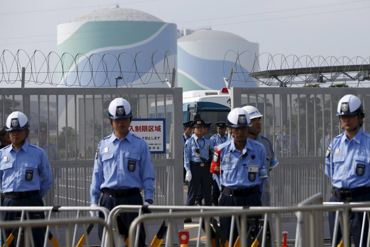 Japonská policie před vstupem do elektrárny Sendai