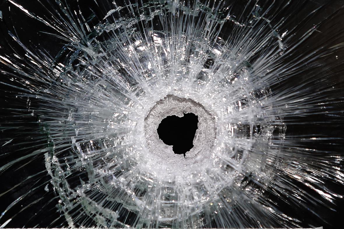 Díra po střele v okně restaurace na Rue de Charonne