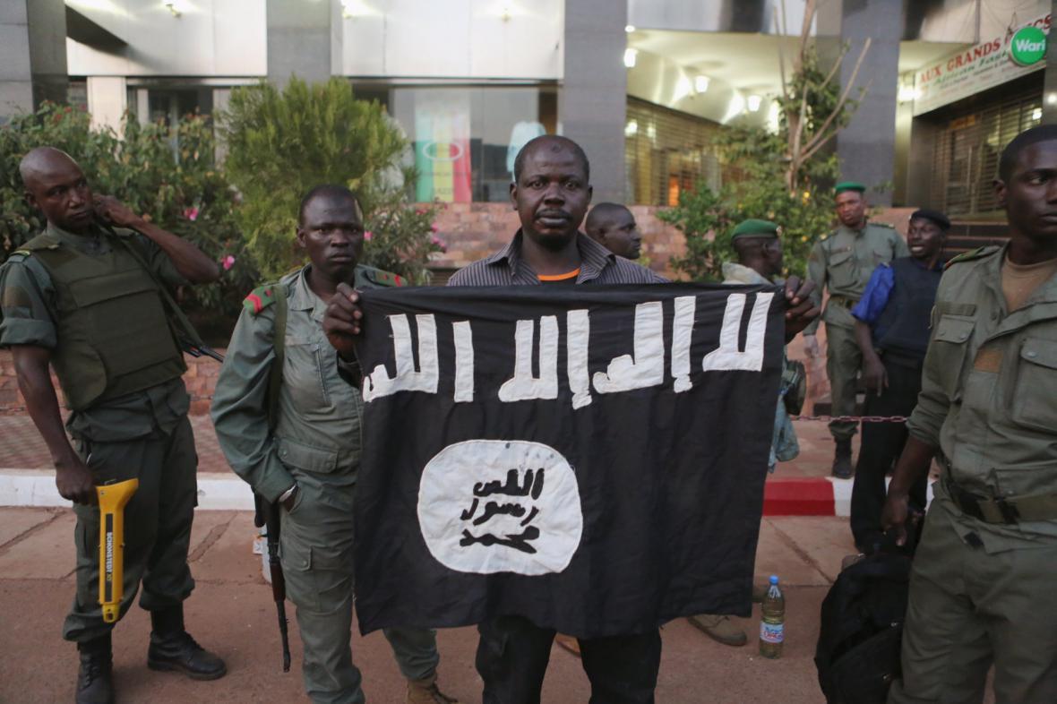 Malijské bezpečnostní síly prezentují džihádistickou vlajku, která patřila atentátníkům z hotelu Radisson