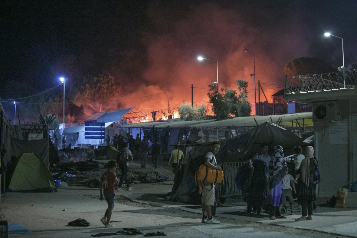 Uprchlíci před hořícím táborem Moria na Lesbu