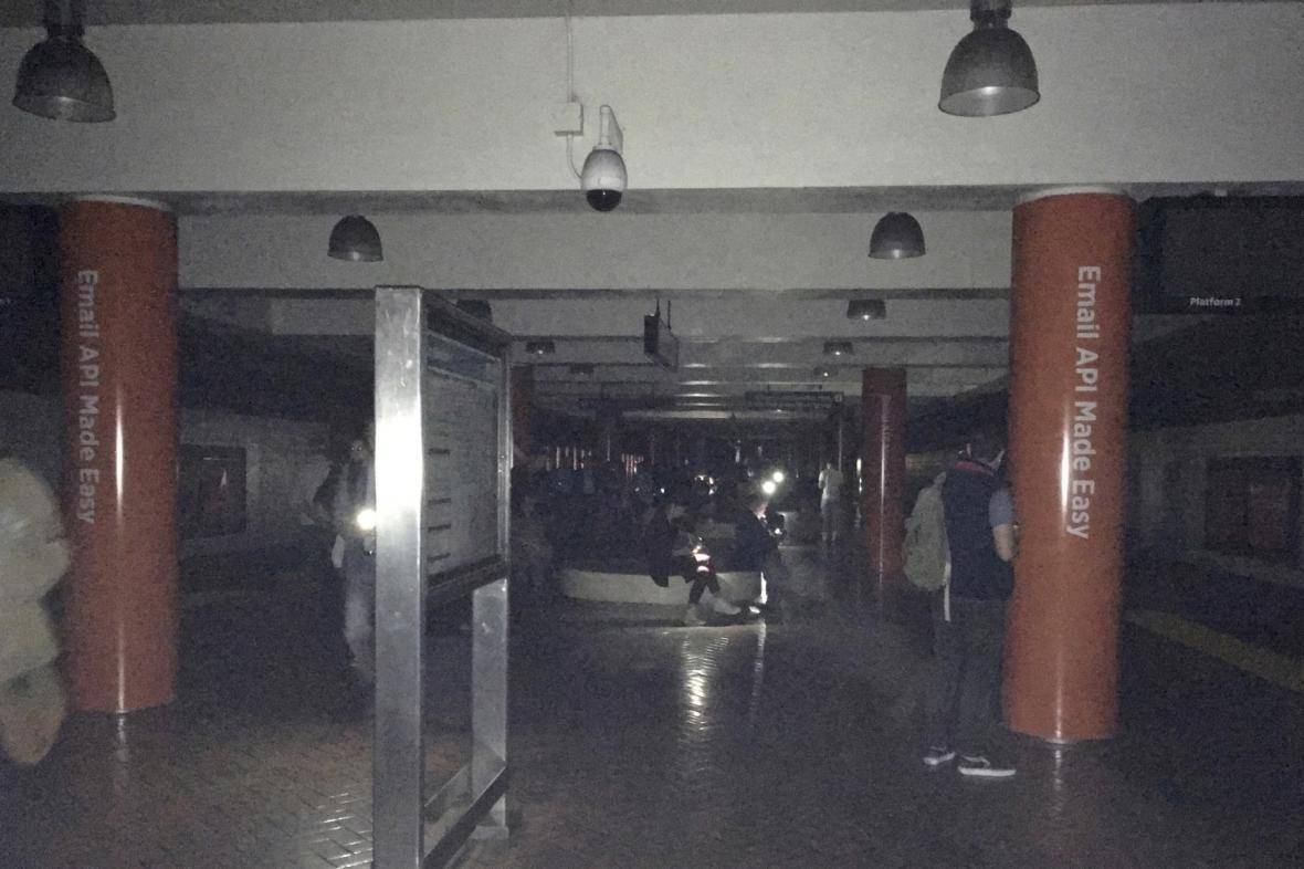 Potemnělým vestibulem metra zářily displeje mobilů