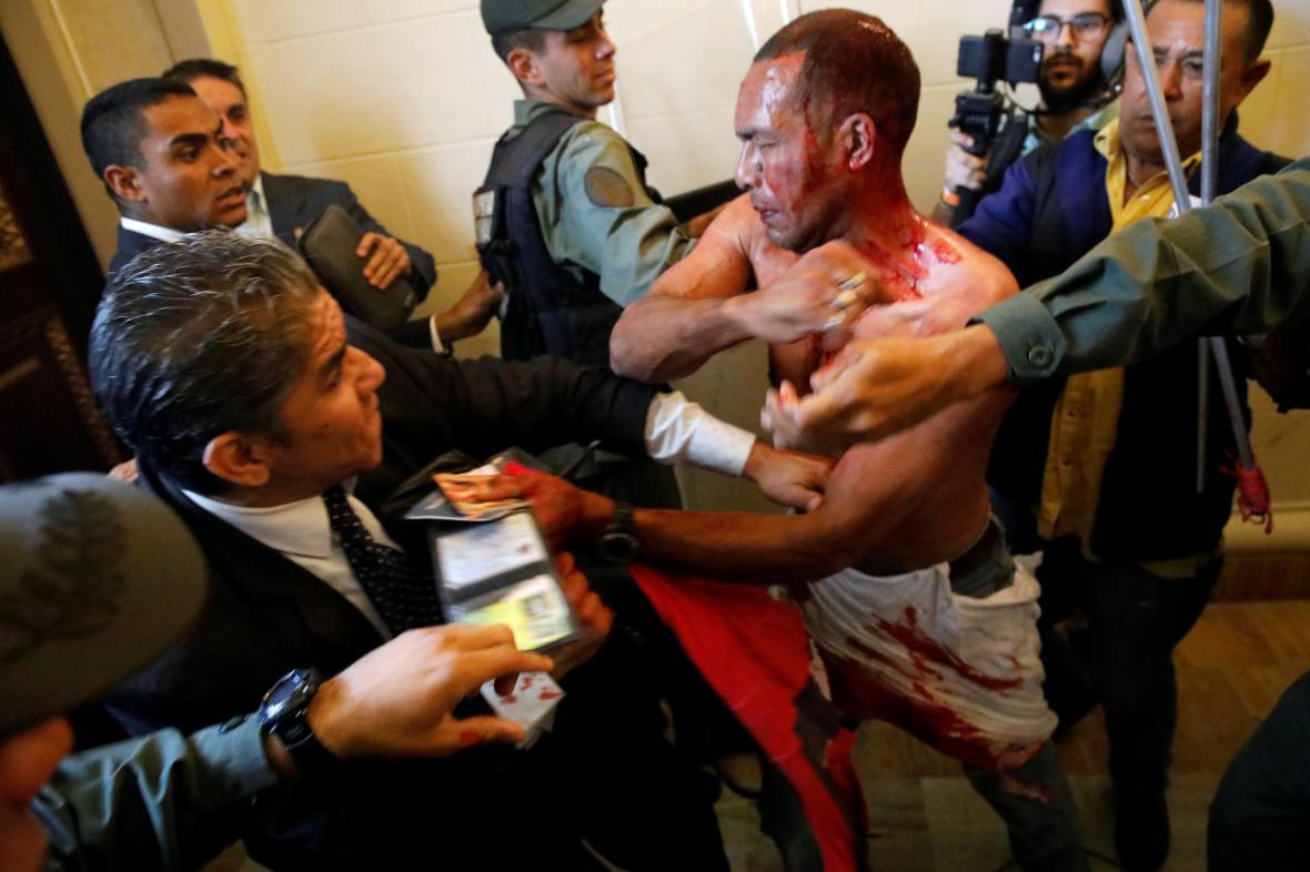 Zraněný vládní stoupenec se pokouší opustit budovu parlamentu, do které se mu se skupinou dalších podařilo proniknout