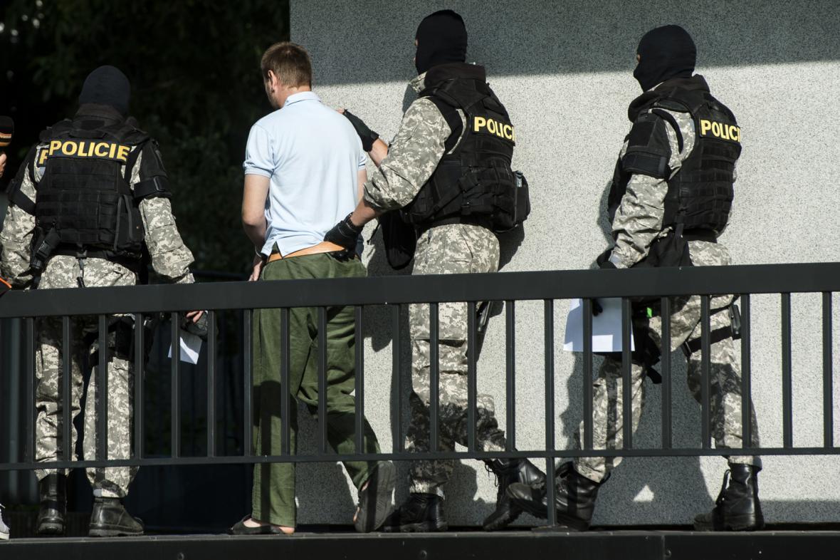 Policejní eskorta odvádí muže obviněného z trojnásobné vraždy v Lázních Bělohrad