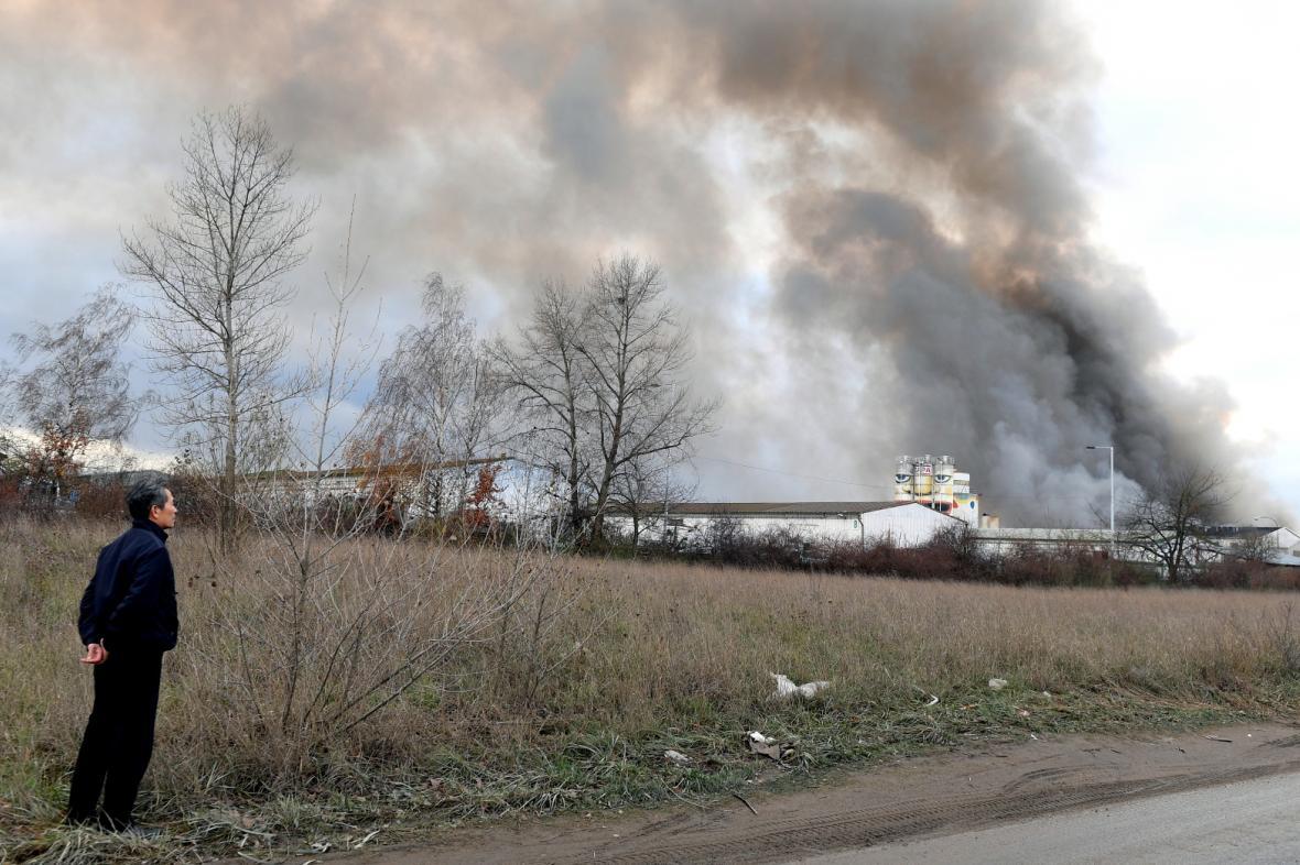 Muž sleduje dým z hořící haly v Písnici
