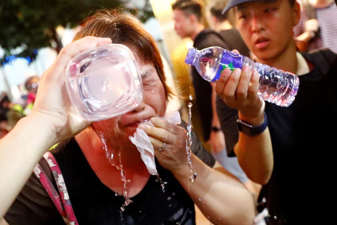 Žena si po zásahu slzným plynem vymývá oči