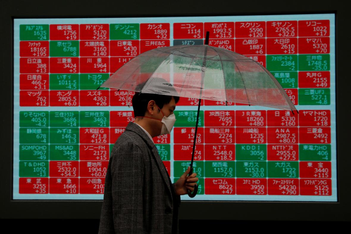 Muž v Tokiu míjí tabuli ukazující pohyby akcií na burzách