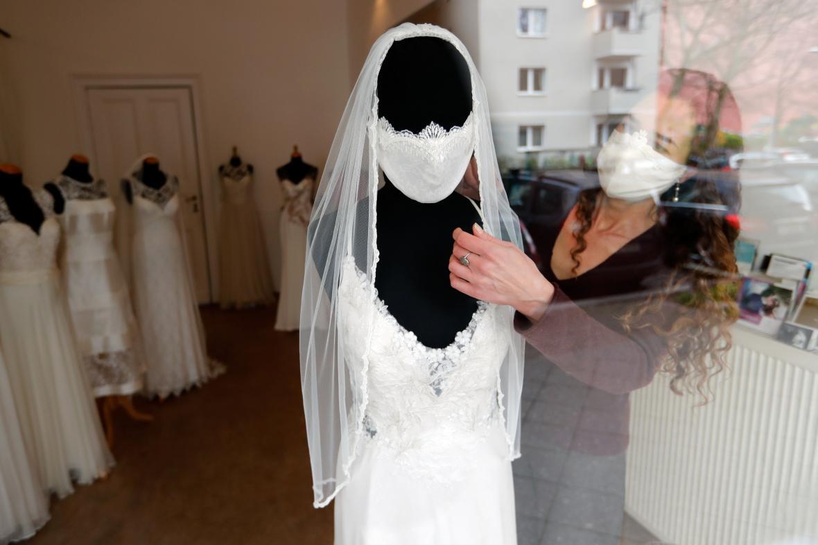 Model svatebních šatů s rouškou v době koronaviru