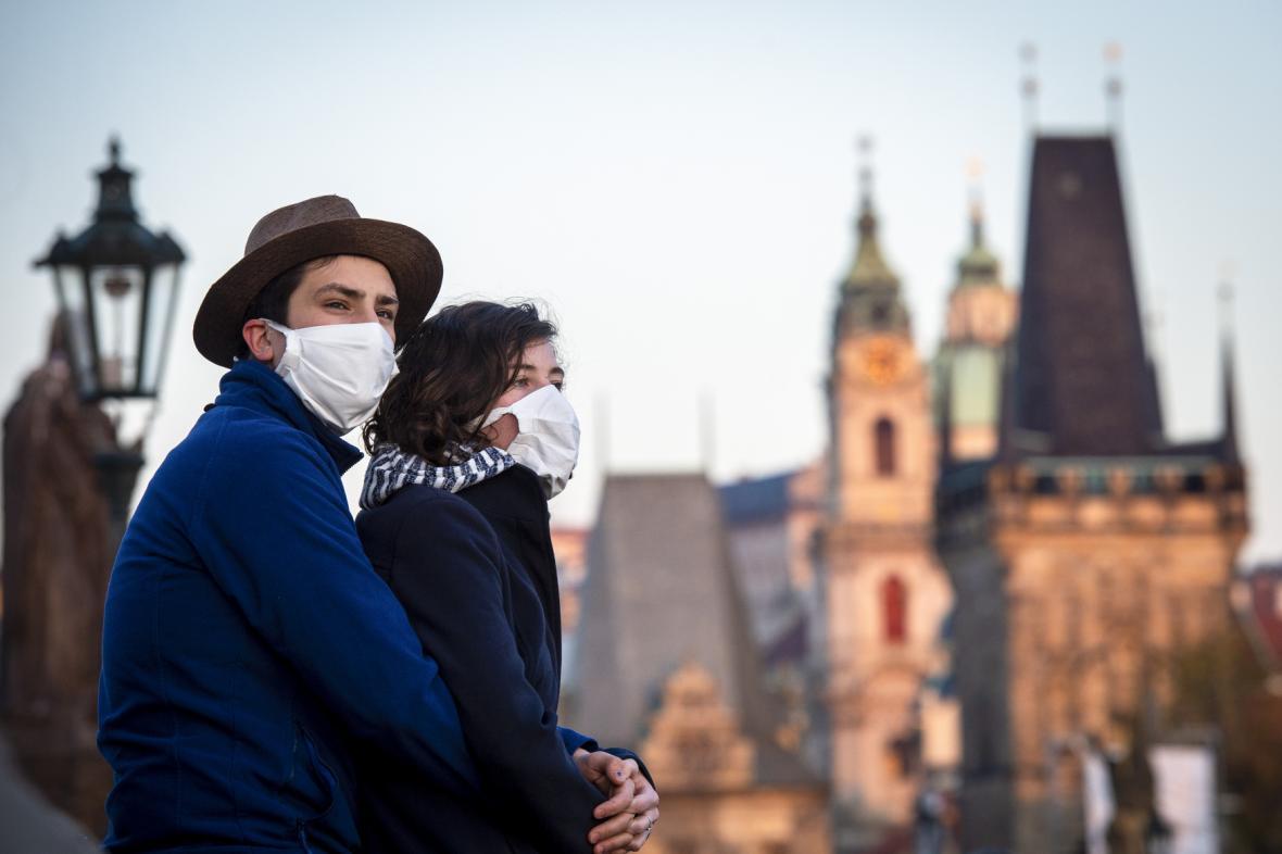 Mladá dvojice s rouškami na Karlově mostě v Praze.