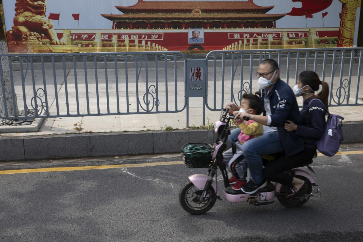 Obyvatelé Wu-chanu před propagandistickým plakátem čínské vlády