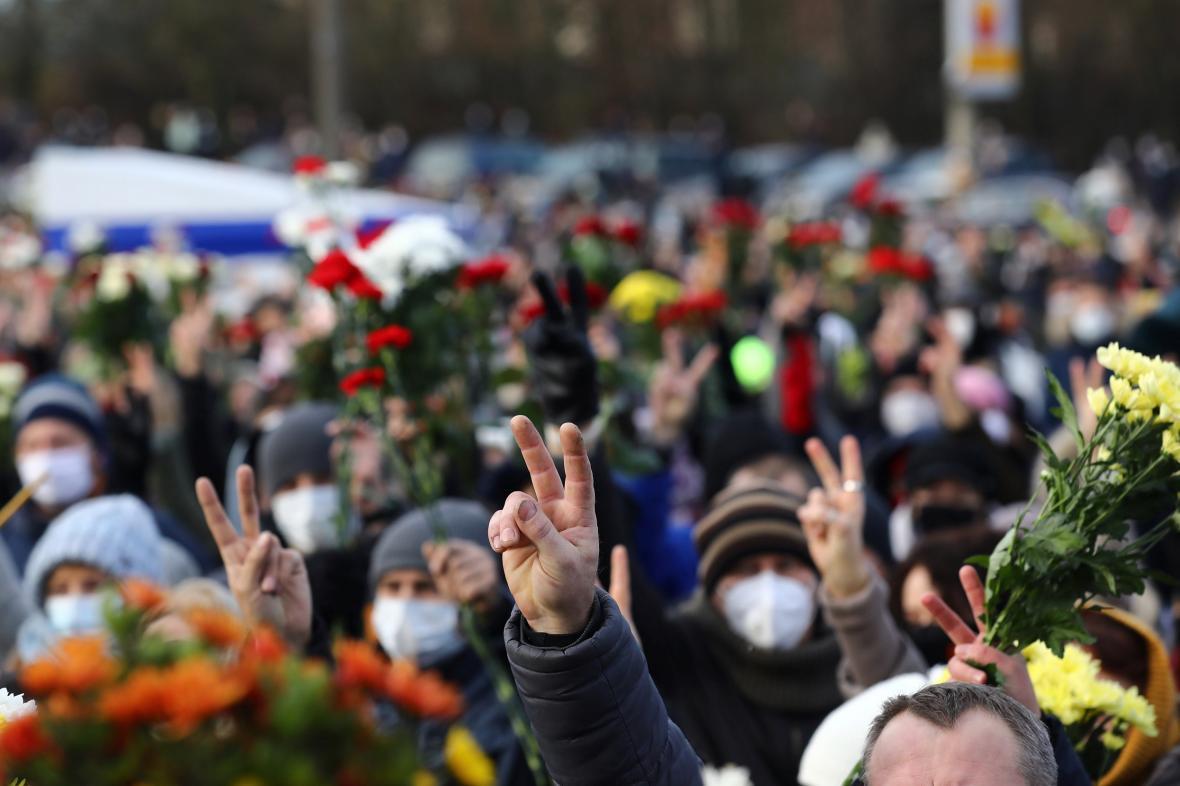 Bělorusové v Minsku zvedají ruce a květiny během vzpomínkové bohoslužby na zemřelého protivládního aktivistu Romana Bondarenka