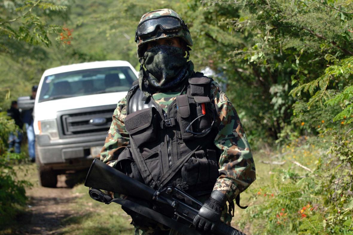 Mexický voják střeží masový hrob