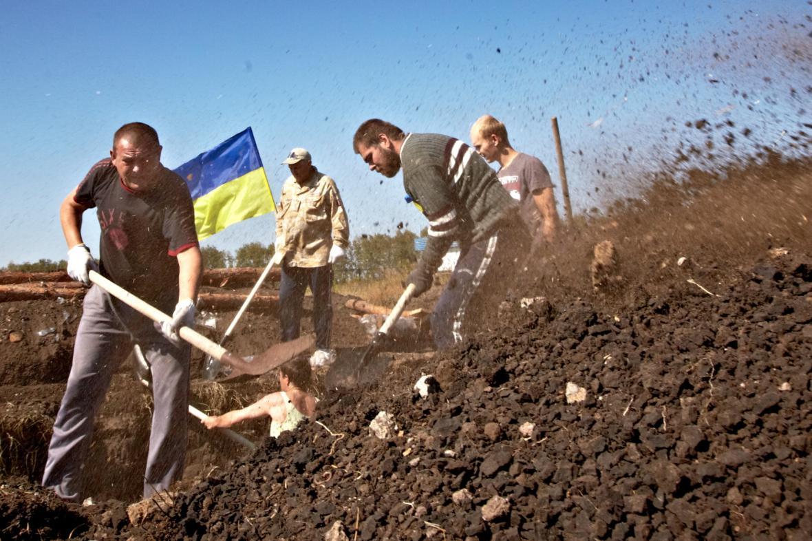 Ukrajinští dobrovolníci hloubí zákopy na hranicích s Ruskem