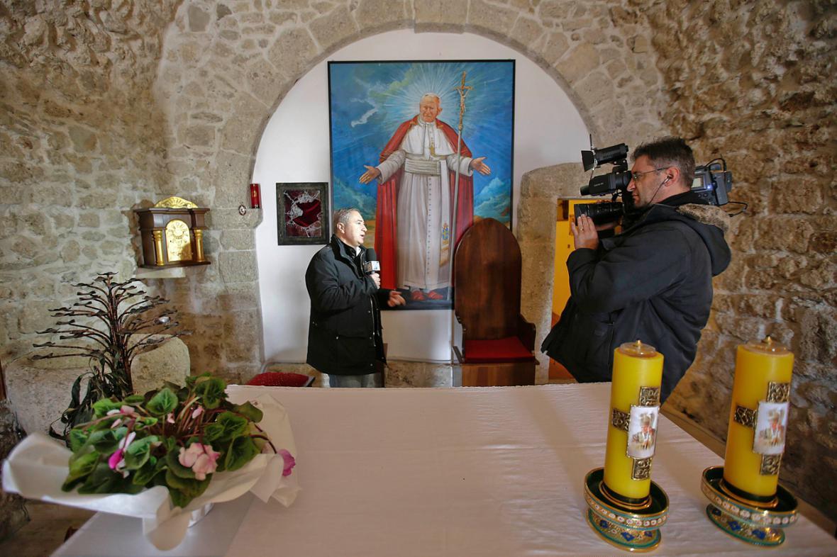 Reportér před rozbitou vitrínou, odkud ukradli relikvii s krví Jana Pavla II.