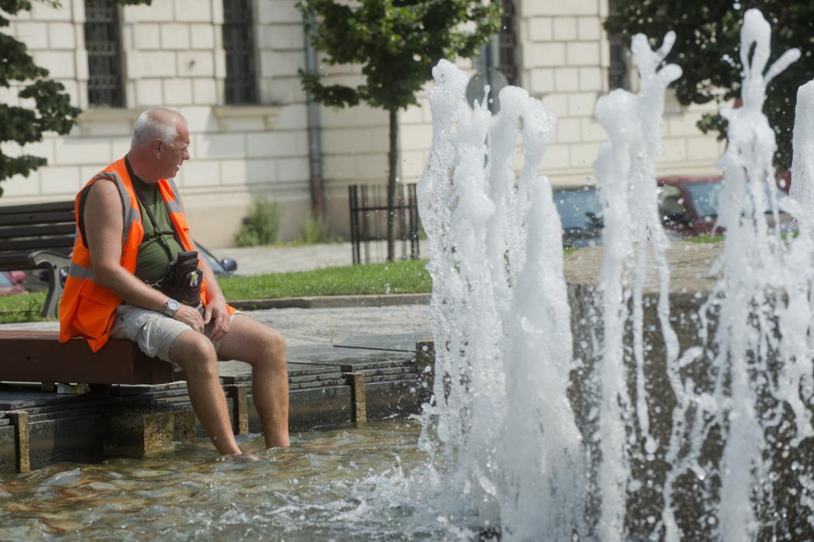 Muž se osvěžuje v horkém počasí