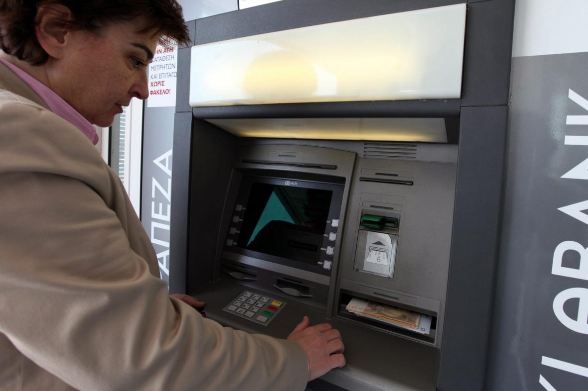 Žena vybírá peníze z bankomatu zavřené kyperské banky