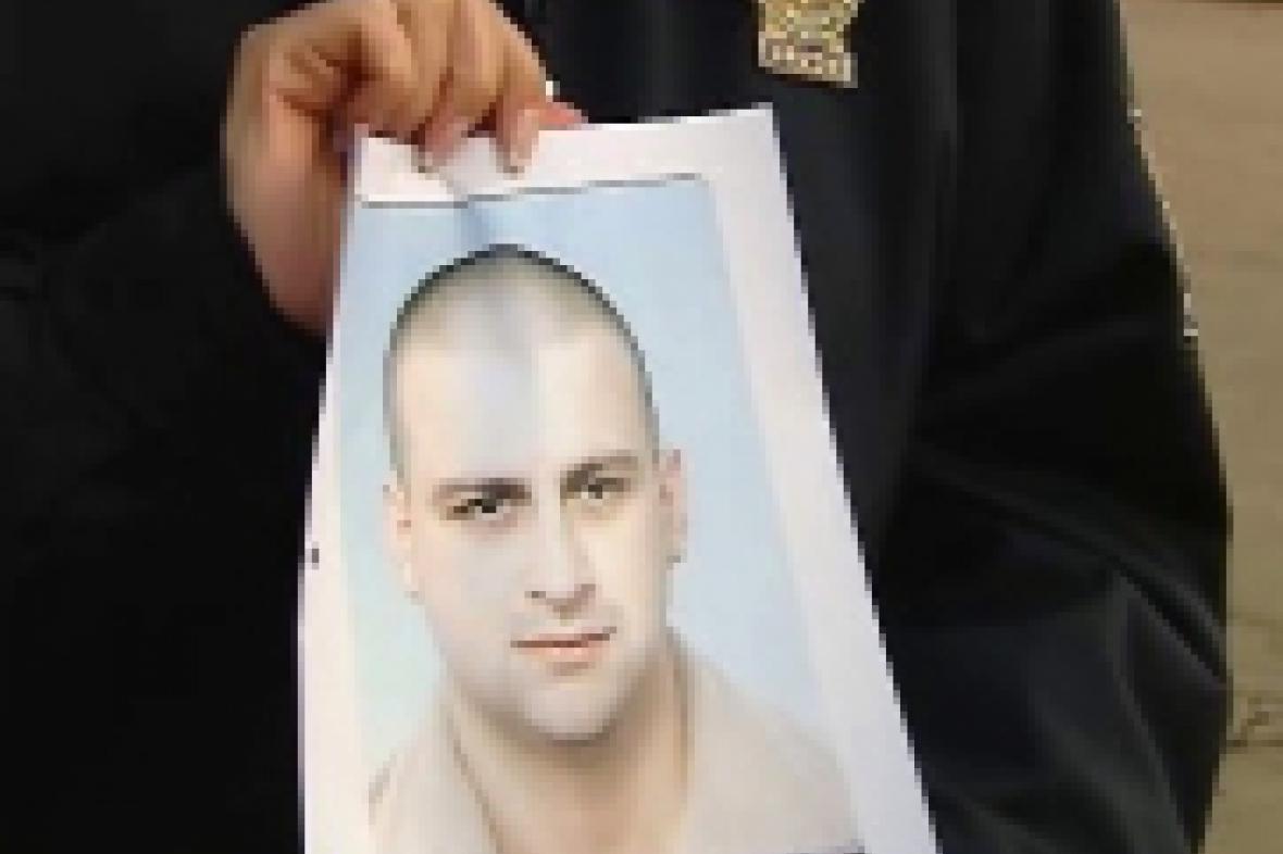 Policista ukazuje protrét hledaného Františka Procházky