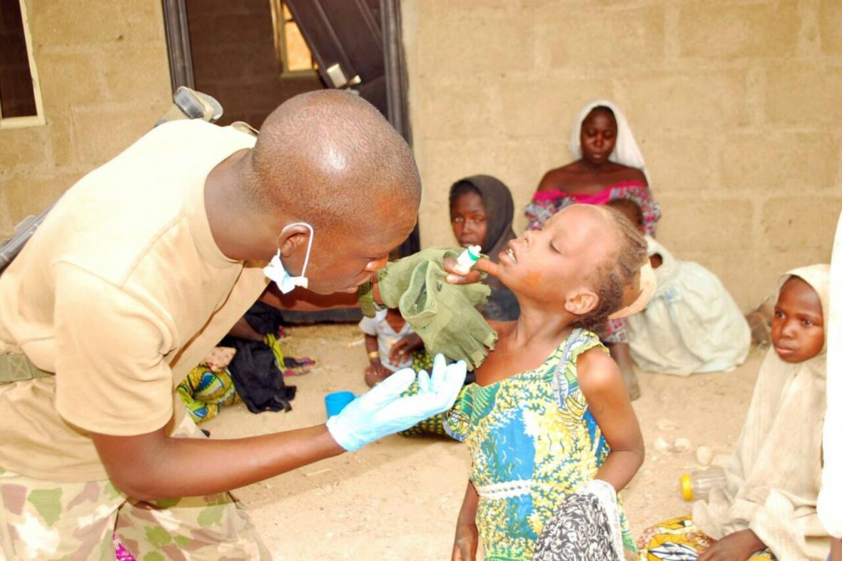 Zdravotník ošetřuje zachráněnou nigerijskou dívku