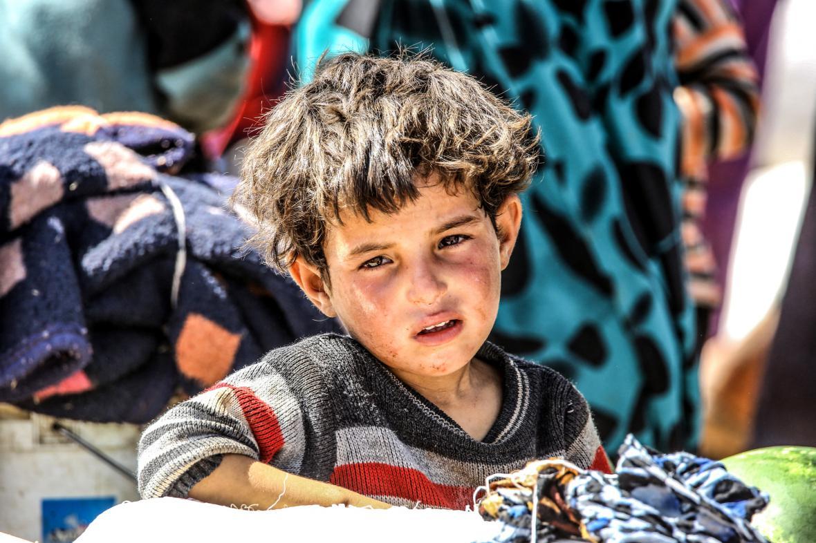 Syrské dítě pozoruje lidi prchající před boji mezi islamisty a Kurdy ve městě Tal Abyad