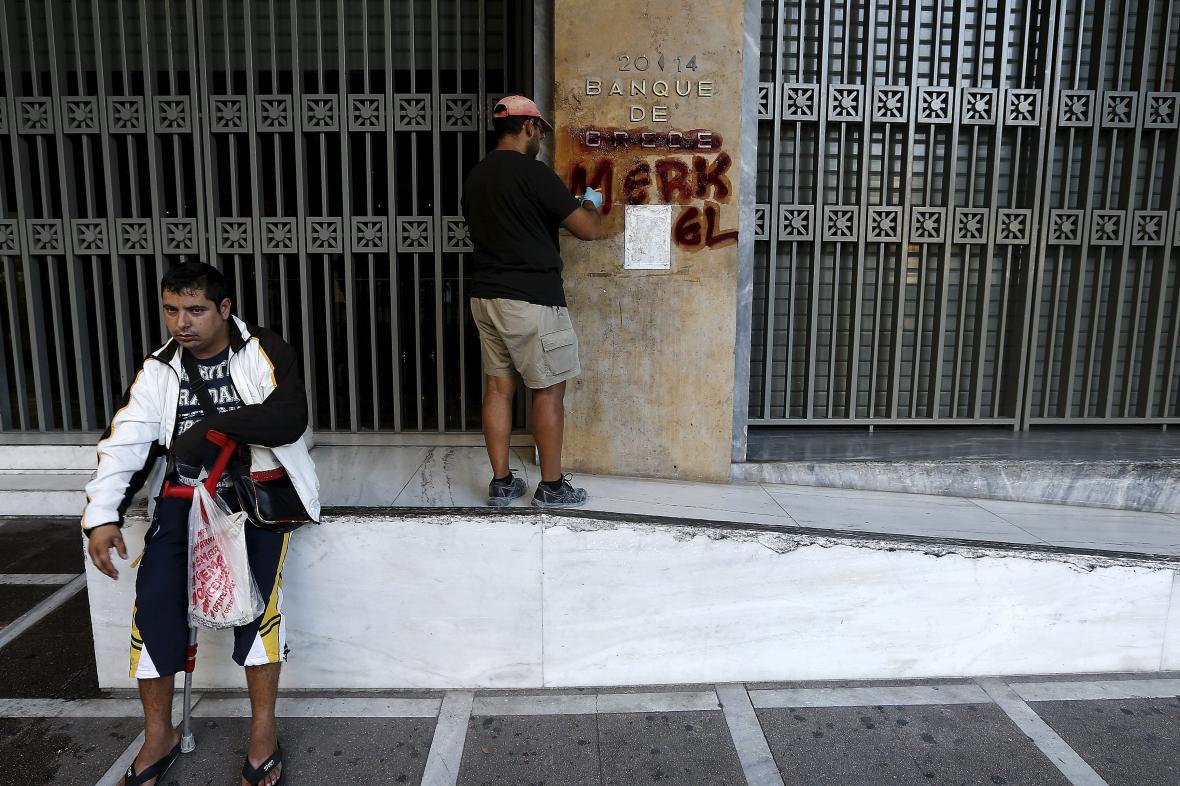 Dělník čistí graffiti na stěně řecké centrální banky