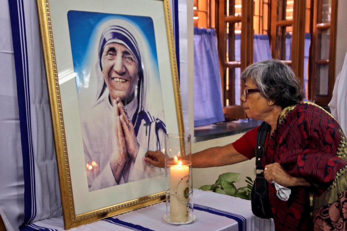 Indická žena se dotýká v Kalkatě portrétu Matky Terezy