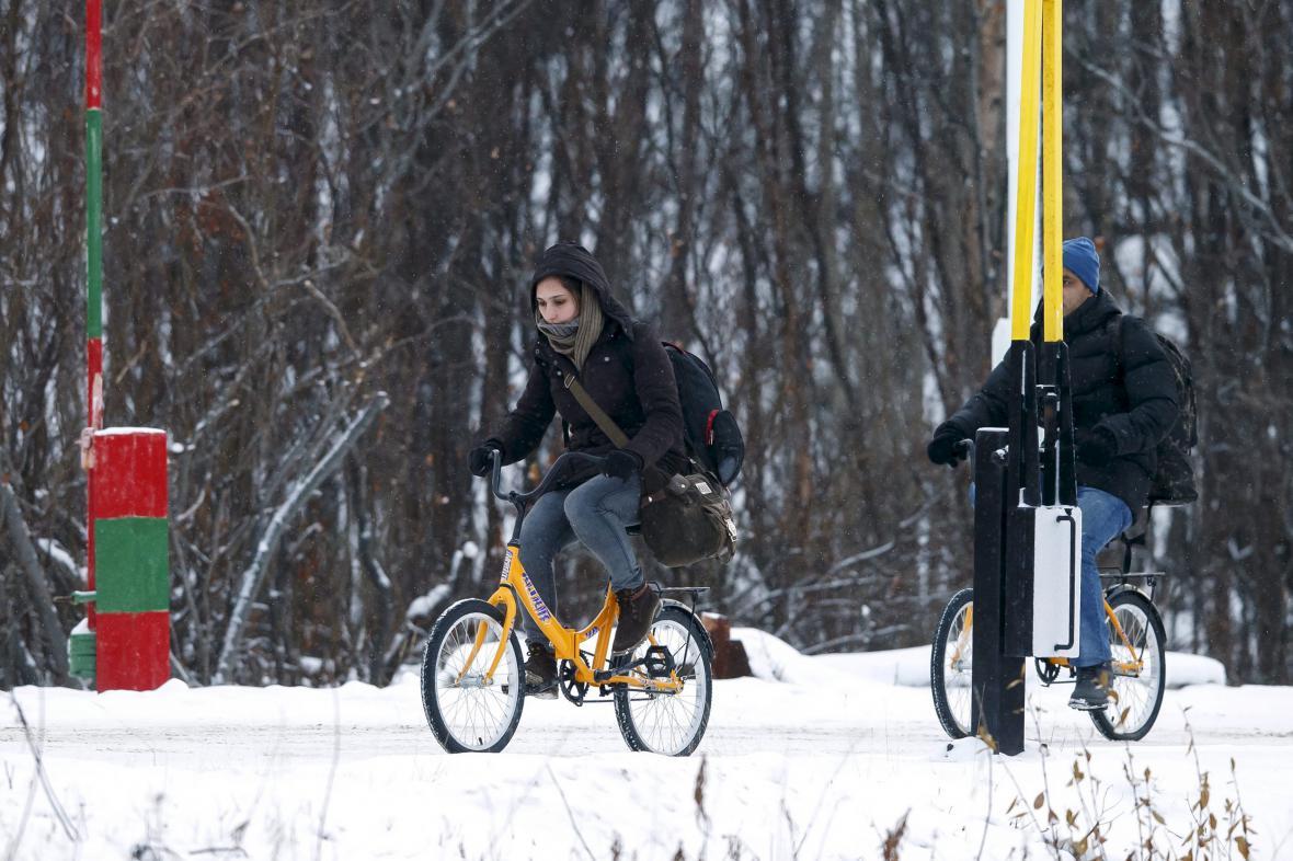 Dvojice uprchlíků přejíždí přes přechod Storskog