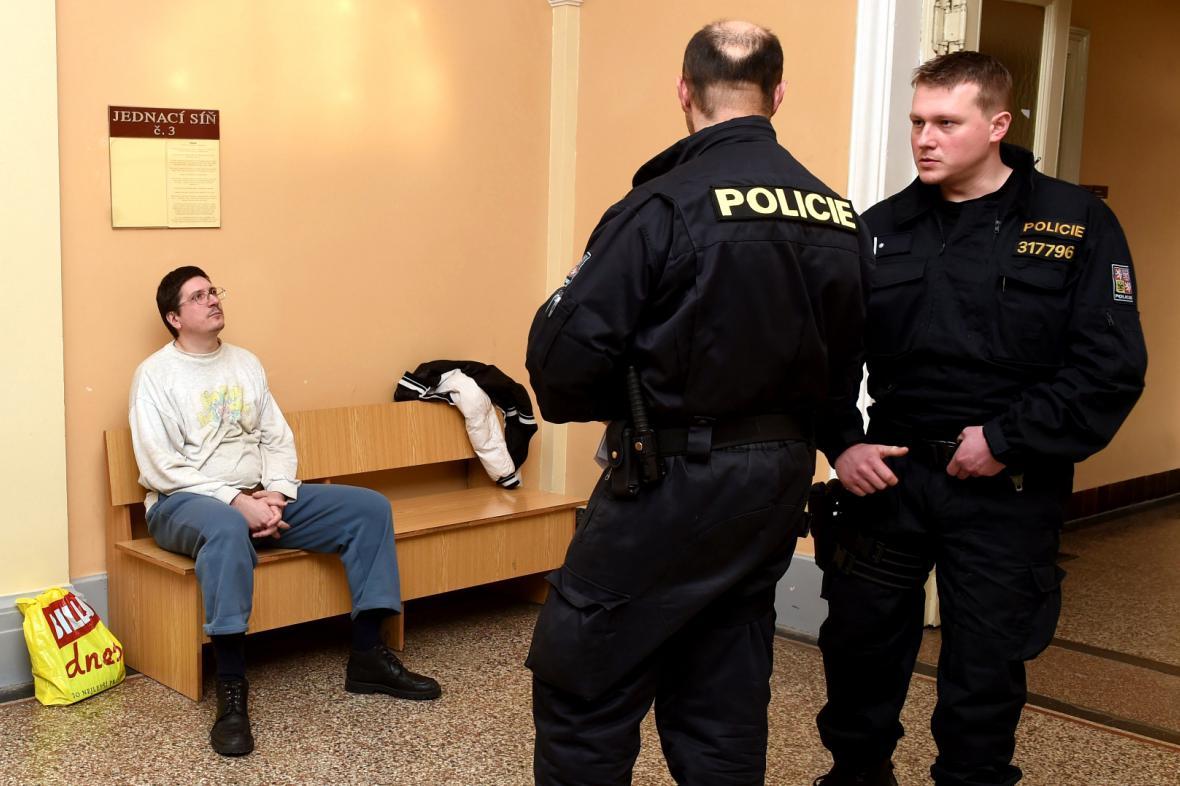 Pavel Nárožný v doprovodu policistů na lavici před soudní síní