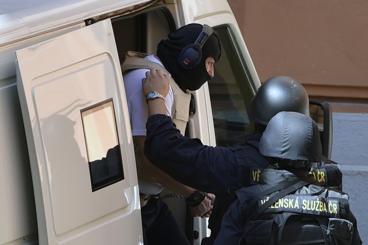 Ozbrojená eskorta přiváží Antonína Dolíhala. Jako spolupracující svědek je chráněn neprůstřelnou kuklou