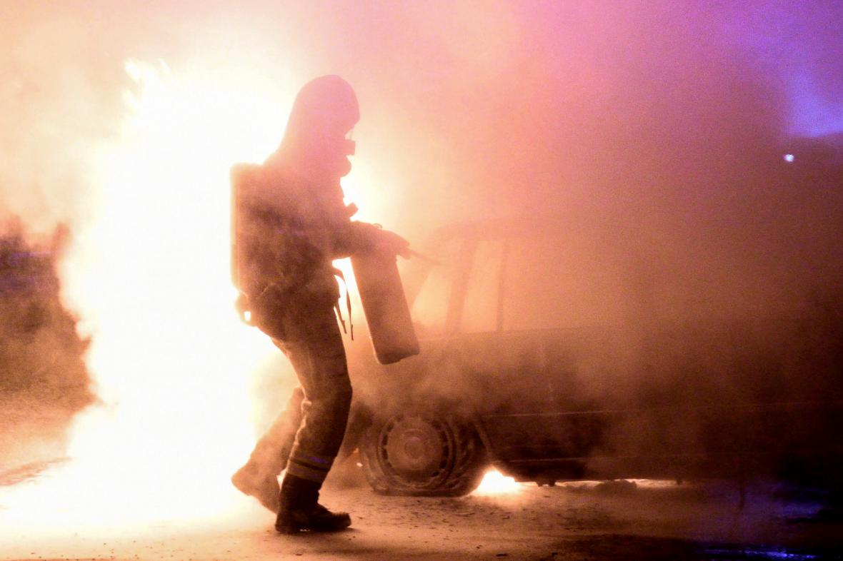 Hasič likviduje požár auta v Malmö