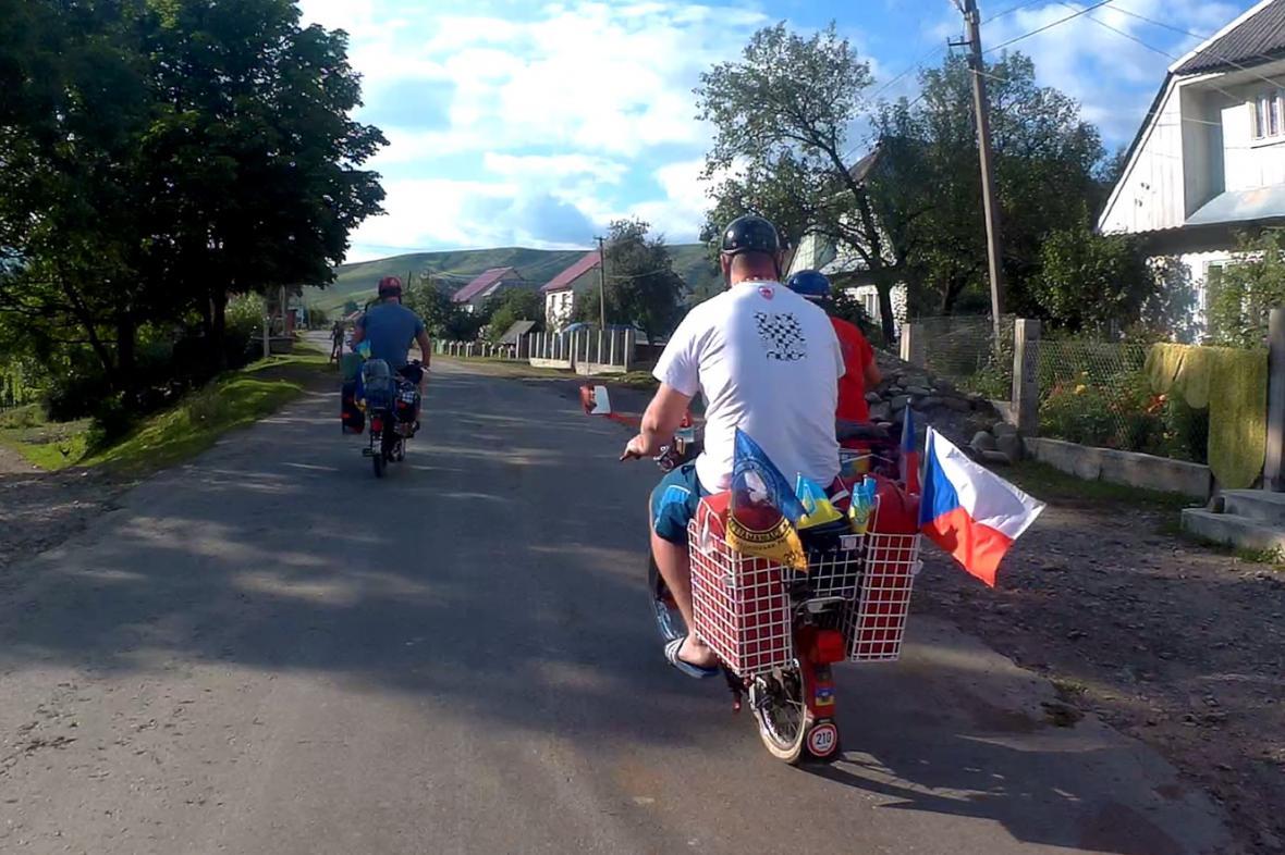 Nadšenci na mopedech projíždějí Koločavou