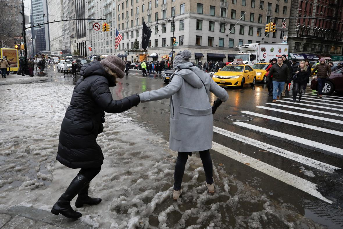 Lidé se snaží přejít v New Yorku namrzlou a zasněženou silnici