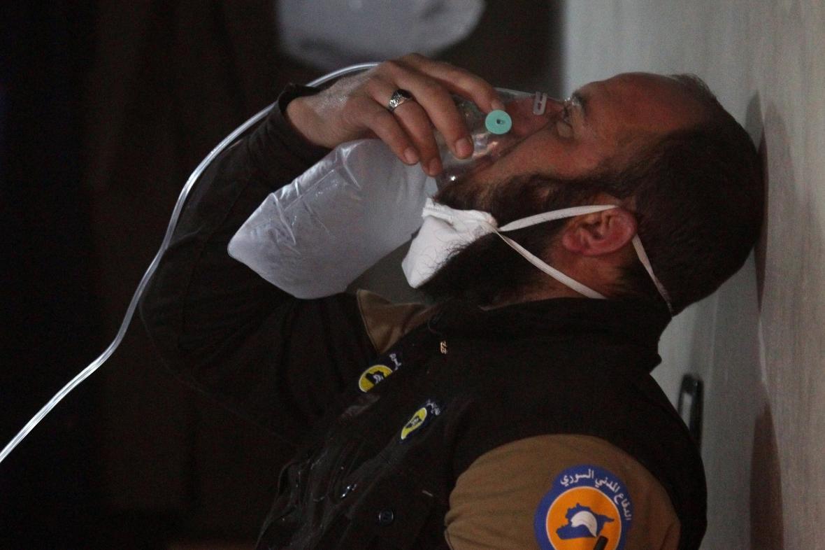 Příslušník civilní obrany používá po útoku armády v Chán Šajchún kyslíkovou masku