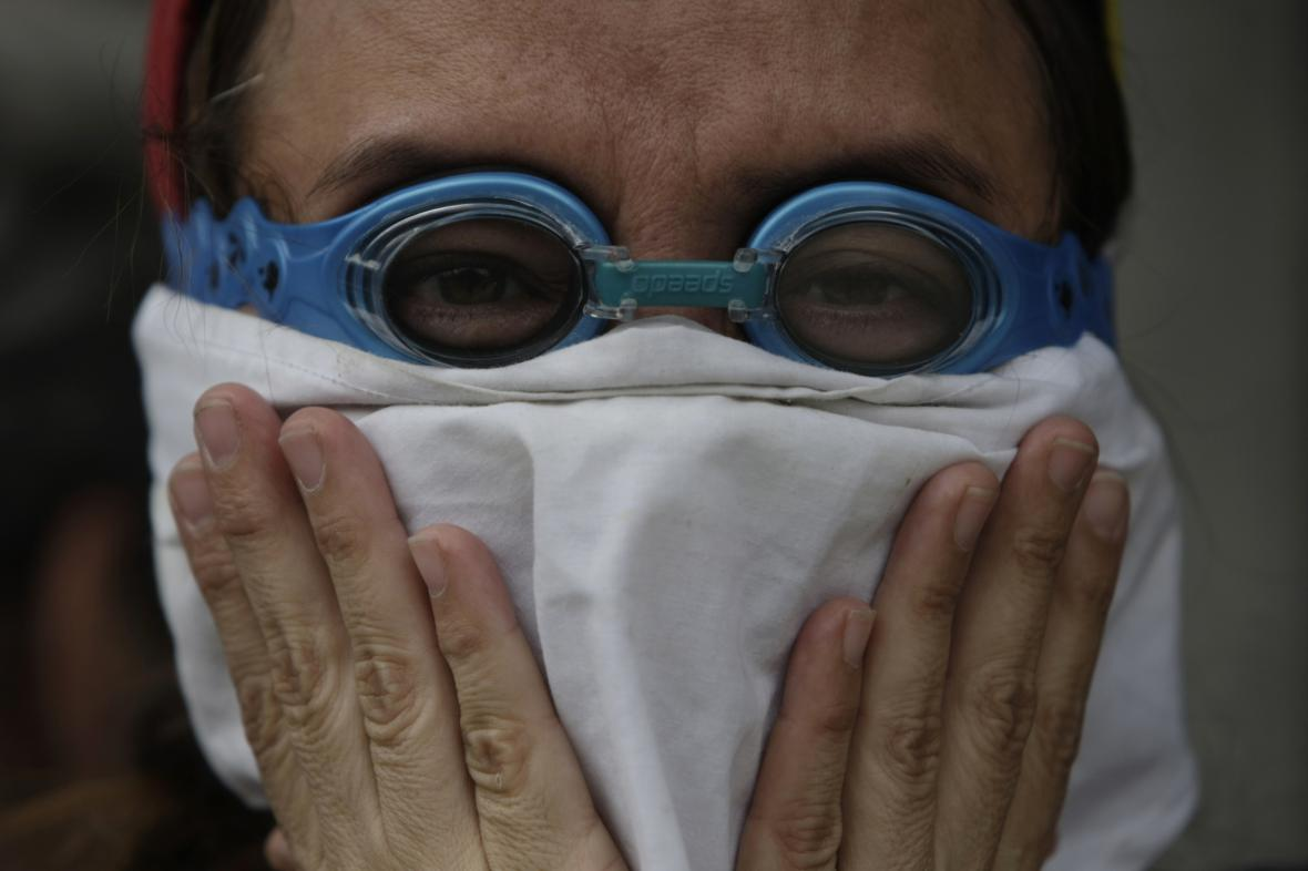 Venezuelský demonstrant se brání před slzným plynem
